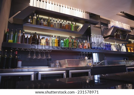Close up on bar with bottle in a line at the nightclub
