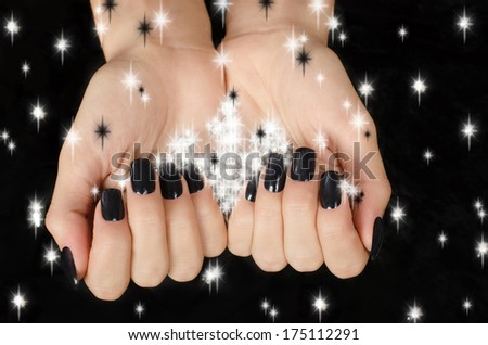 Close up on beautiful female hand with black manicure. - stock photo