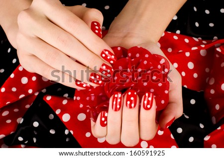 Close up on beautiful female hands with cute red manicure with white dots. Black and red dotted background. - stock photo