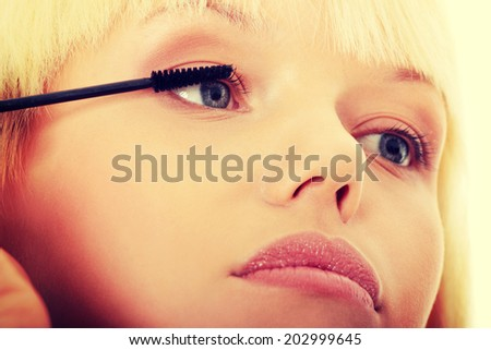 Close up on beautiful young woman doing make up on eyelashes. Over white background. - stock photo