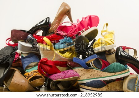 Close up on big pile of colorful woman shoes. Untidy stack of shoes thrown on the ground. - stock photo
