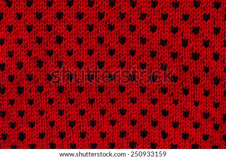 Close up on black and red heart dots woolen texture. Knit shapes pattern as a background. - stock photo