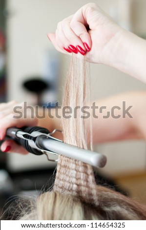 Close up on bride wedding hairdo with electric hair curler - stock photo