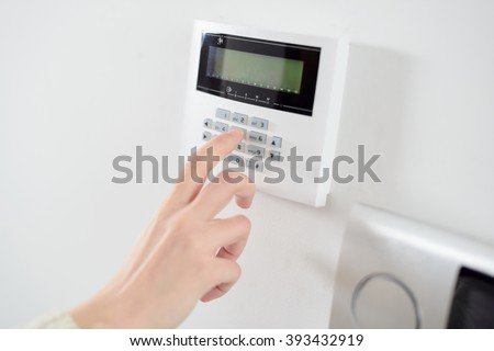 Close up on brunette woman's hand entering code on keypad of home security alarm. Video intercom next to alarm keypad. - stock photo