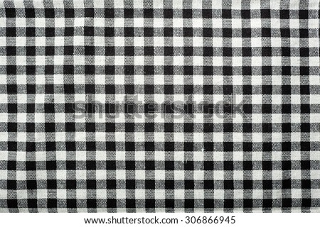Close Up On Checkered Tablecloth Fabric. Black With White Tartan Square  Pattern As Background.