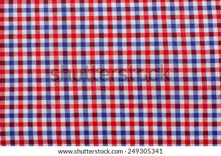 Close up on checkered tablecloth fabric. Red and blue with white tartan square pattern as background. - stock photo