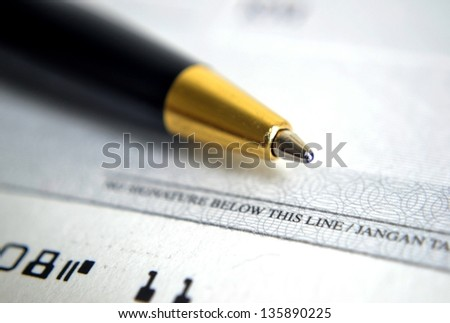 Close up on cheque with a pen - stock photo