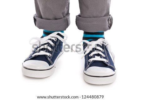 Close-up on child feet with sneakers. Studio shot.