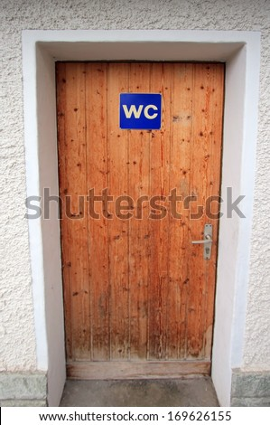 Close up on closed wooden door with WC sign - stock photo