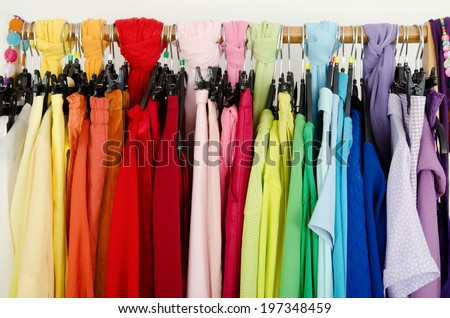 Close up on color coordinated clothes on hangers in a store. Detail on all colors clothes hanging on a rack nicely arranged. - stock photo