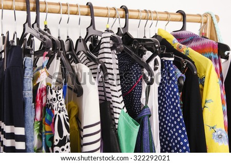 Close up on colorful clothes on hangers in a store. Clothes and accessories hanging on a rack nicely arranged. - stock photo