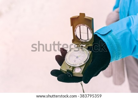 Close up on compass instrument in gloved hand . Mountain hiking trails. Winter mountain trip concept - stock photo
