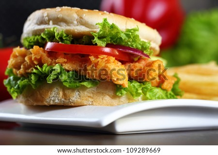 Close up on crispy chicken burger with lettuce and tomato. - stock photo