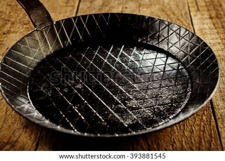 Close up on empty single black cast iron pan with scoring lines inside over dark thick brown wooden table - stock photo