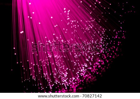 Close up on ends of many illuminated vibrant pink fibre optic strands against black. - stock photo