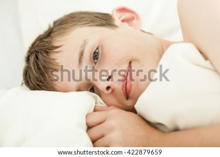 Close up on face and hand of grinning brunette boy in bed with head on pillow and white blanket