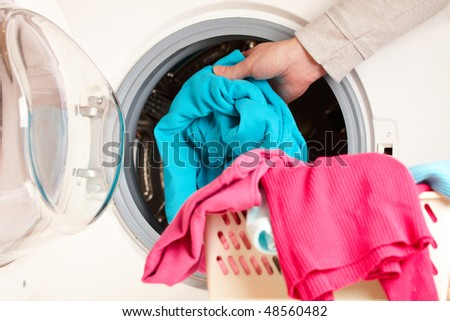 Close-up on female hand putting colorful clothes into washing machine drum - stock photo