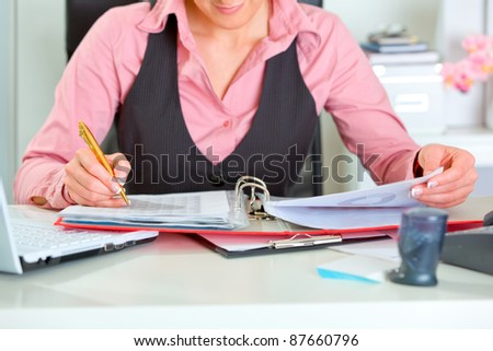 Close up on female working at office desk with documents - stock photo