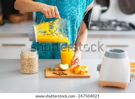 Close-up on fitness young woman pouring pumpkin smoothie in glass - stock photo