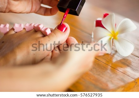 close up on foot of a woman painting her big toenail with nail polish standing