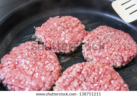 Close up on four hamburgers in the making.