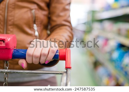 close up on hand of a woman on a supermarket trolley carries - stock photo
