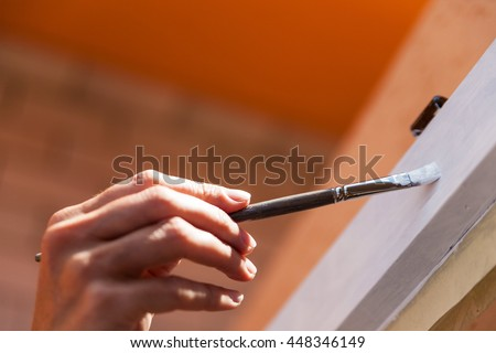 Close up on hand using little paintbrush with white paint while painting side of door inside room with copy space