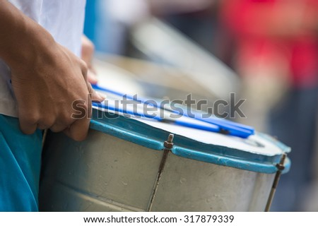Close up on hands from performer drumming and celebrating the opening of the carnival of Salta in the street with colorful costumes. North of Argentina 2014 - stock photo