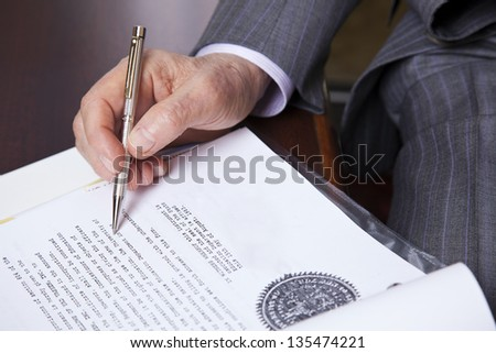 Close up on hands of a senior (in his 80's) businessman holding a fancy pen in his right hand, about to sign a contract. Seen from a high angle. - stock photo