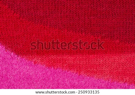 Close up on knit woolen texture. Pink magenta to red woven thread sweater as a background. - stock photo
