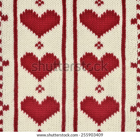 Close up on knit woolen texture. Red heart pattern as a background. - stock photo