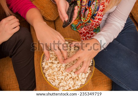 close-up on ladies hands on popcorn while watching tv/home cinema with remote control in hand - stock photo