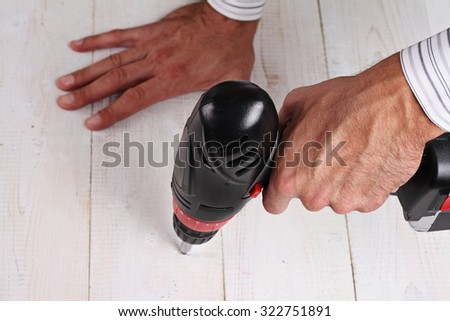 Close up on male hand using electric  drill. Man Doing DIY at home