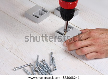 Close up on male hands using electric screwdriver, fixing furniture. DIY tools, housework equipment - stock photo
