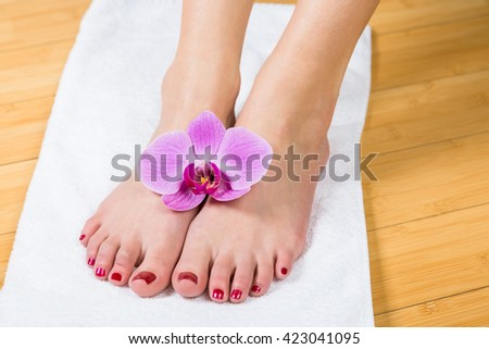 Close up on neatly painted toenails on female feet with purple flower between them over white towel - stock photo