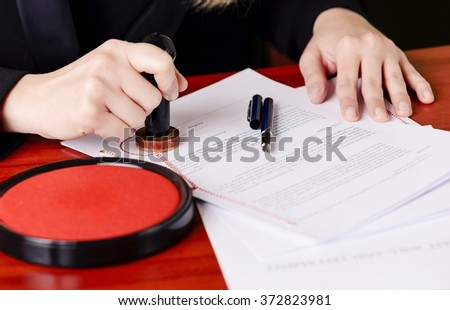 Close up on notaries  public hand stamping the testament and last will - stock photo