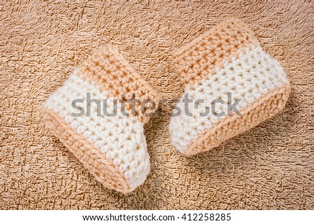 Close up on pair of cute brown knitted baby booties over plush brown towel background