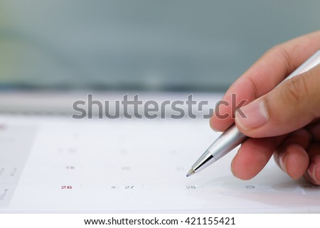 close up on pen writing on calendar for note or make appointment concept. - stock photo