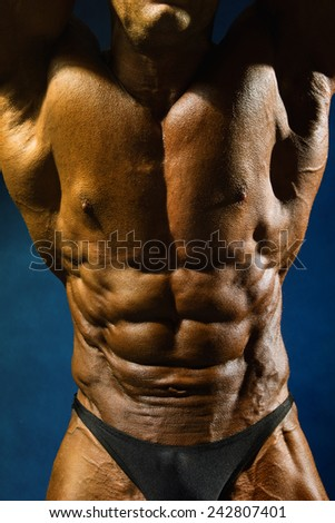 Close up on perfect abs. Strong bodybuilder on a blue background. - stock photo