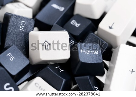 Close-up on Pile of Black and White Computer Keyboard Keys. Up Arrow and Home Keys are in focus - stock photo