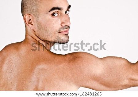 Close up on profile of a man and the arm with the shoulder and biceps. Looking at camera. - stock photo