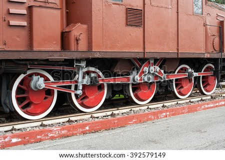 Close up on set of steel flanged wheels under old fashioned red and white locomotive train with blank copy space area - stock photo