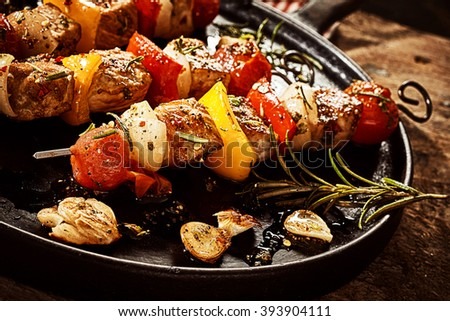 Close up on single round black cast iron frying pan filled with kebabs, garlic, and rosemary sprig