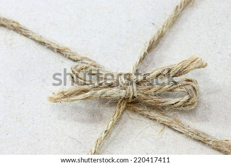 close up on String tied in a bow  brown recycled paper - stock photo