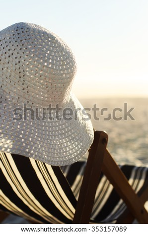 Close up on summer hat hanging on beach chair at sunset  - stock photo