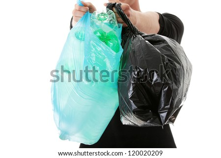 Close up on teen man carrying a plastic trash bags full with empty recyclable household material.