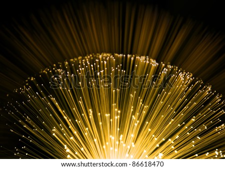 Close up on the ends of many illuminated fiber optic strands with black and yellow blur background. - stock photo