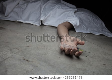 Close-up on the floor of the drugs in hand of the dead body. In the background, a young drug addict - stock photo