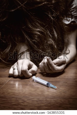 Close-up on the floor of the syringe with the drug. In the background, a young drug addict - stock photo