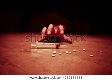 Close-up on the floor of the syringe with the drug. In the background, a young drug addict, red tone color processed - stock photo